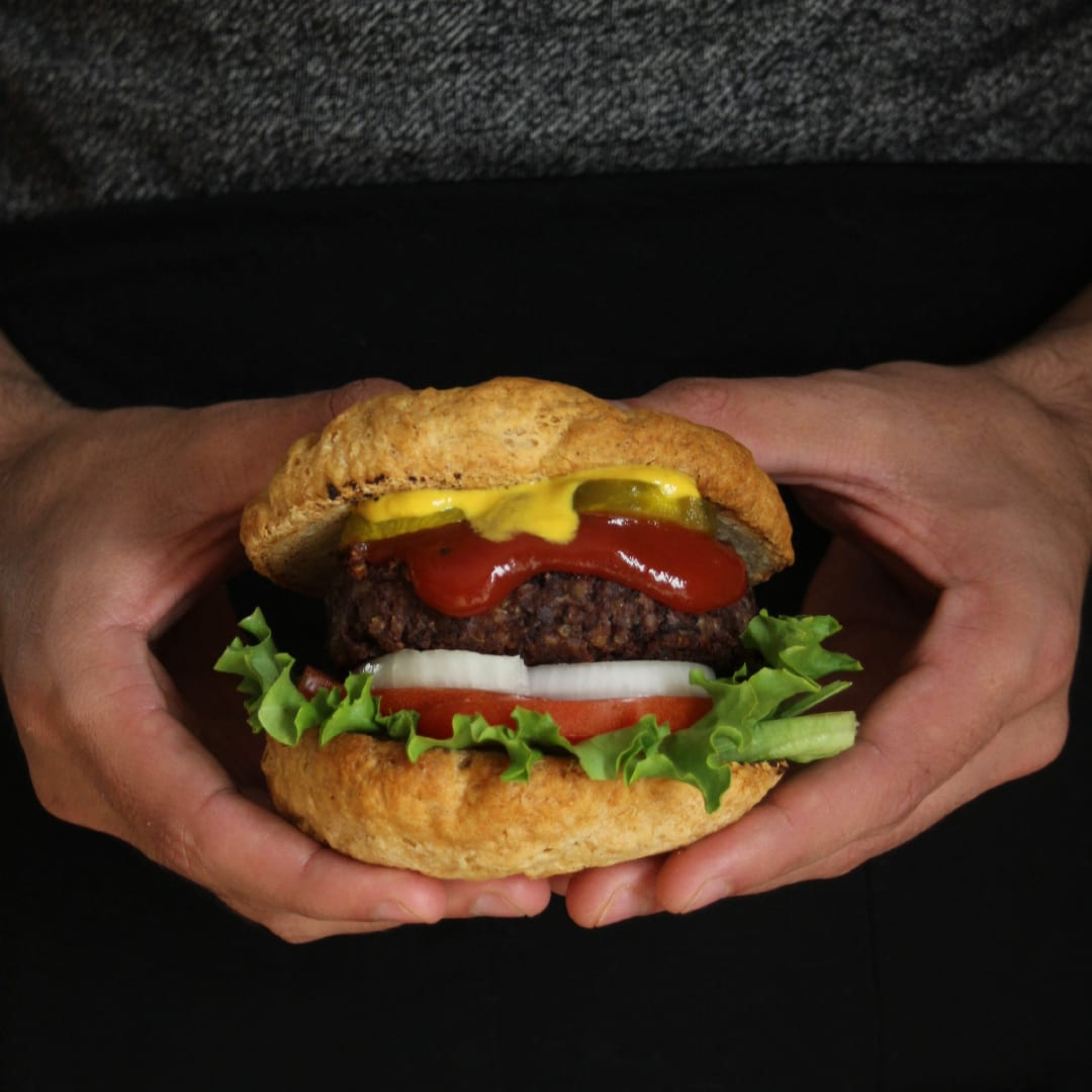 QSB black bean burger held between 2 hands