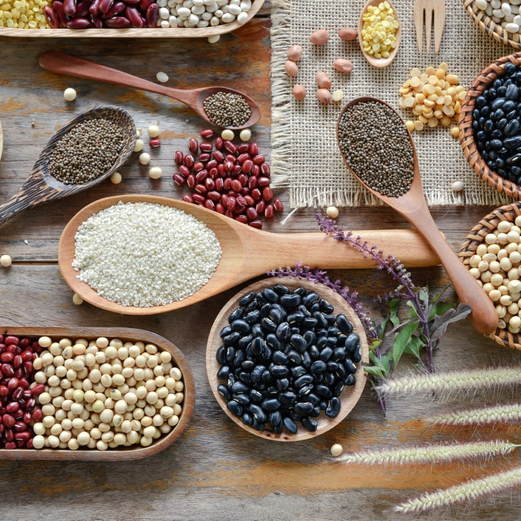 Top view of various legumes and seeds with a wooden cookware